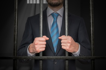 Businessman or politician behind bars in prison cell.
